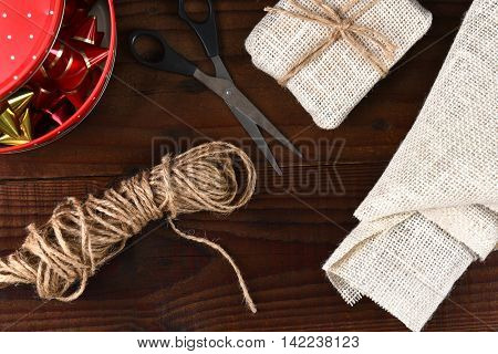 Fabric wrapped present with a tin of ribbon and bows. Top view on a rustic dark wood table.