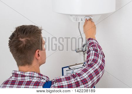Young Male Plumber Holding Clipboard Adjusting Temperature Of Electric Boiler