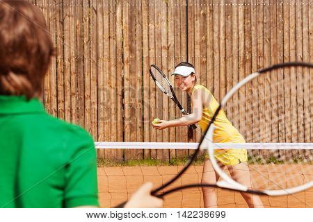 Tennis players, teenage girl and her opponent, playing a match on the clay court in summer