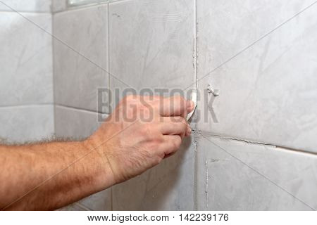The male hand with the rubber stick applies grout on a seam between tiles in a bathroom. Home repairs.