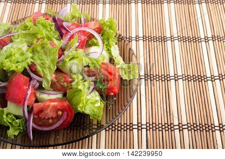 Top view of the transparent plate with the vegetarian salad with fresh tomatoes onion and lettuce on a bamboo mat on a tabletop
