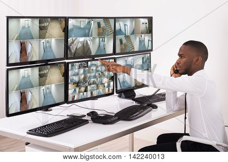 Security System Operator Talking On Phone While Looking At CCTV Footage