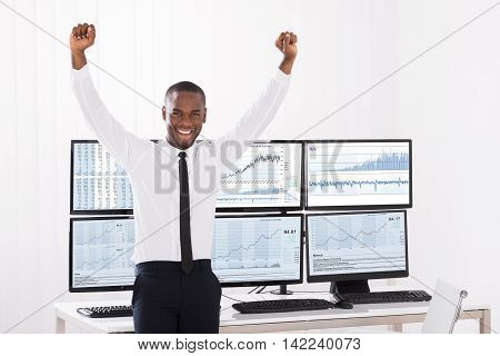 Portrait Of Happy Young Male Stock Market Broker With Raised Arm In Office