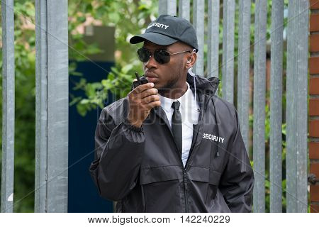 Young Male Security Guard In Black Uniform Using Walkie-Talkie