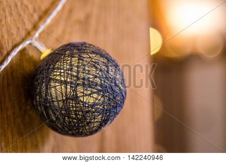 Decorative light fixture, cotton ball on string against a wooden background
