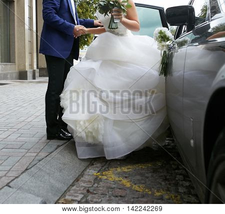 Beautiful couple, bride and groom getting into wedding limousine.