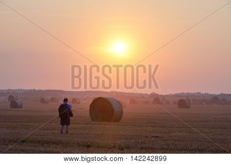 Amazing rural scene on autumn field with straw roles