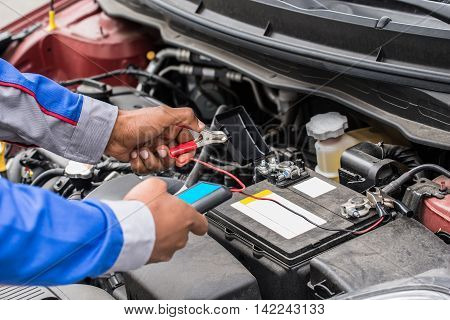 Close-up Of Mechanic Hands Using Multimeter For Checking Battery In Car