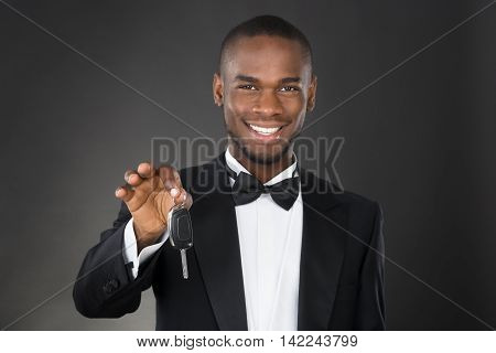 Portrait Of Happy African Waiter Holding Car Key In Hands Over Black Background