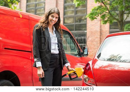 Photo Of Smiling Young Businesswoman Refueling Car's Tank