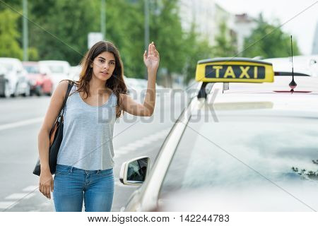 Young Woman Raising Arm To Hail Taxi On Street