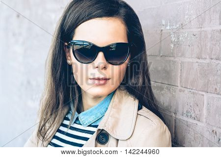 Portrait of a young beautiful brunette woman in sun glasses and a coat outdoors