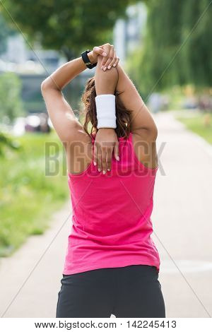 Rear View Of Sporty Young Woman Doing Morning Exercise In Park
