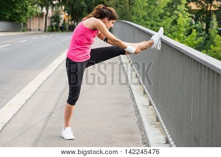 Young Woman Stretching Her Legs Over Fence At Road