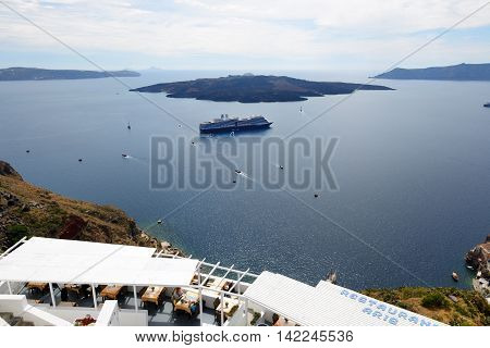 FIRA GREECE - MAY 17: The view on Fira town and tourists enjoying their vacation on May 17 2014 in Fira Greece. Up to 16 mln tourists is expected to visit Greece in year 2014.