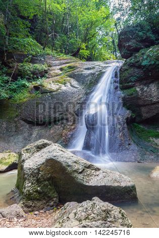 Waterfall from a cliff in the mountains. Cascade on the river. Stones covered with moss in the lake with clear water. Water in Motion. Republic of Adygea Southern Russia.