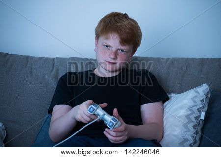 Boy Sitting On Sofa At Home Playing Videogames