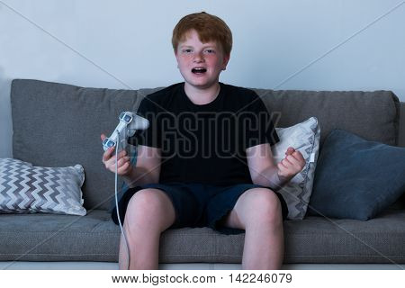 Boy With A Joystick Sitting On Sofa Playing Videogames