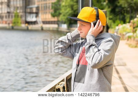 Boy Wearing Yellow Cap Looking At Lake While Listening To Music