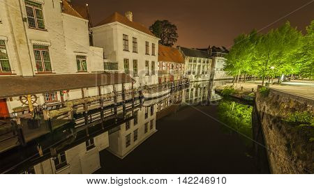 Romantic nocturnal view of a canal in Bruges. Buildings trees and boats are reflected in the water