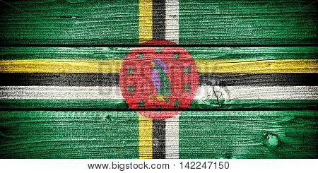 flag of Dominica painted on old grungy wooden background: 3d illustration