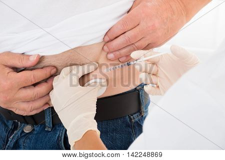 Close-up Of Doctor's Hand Injecting Stomach Of Diabetic Patient