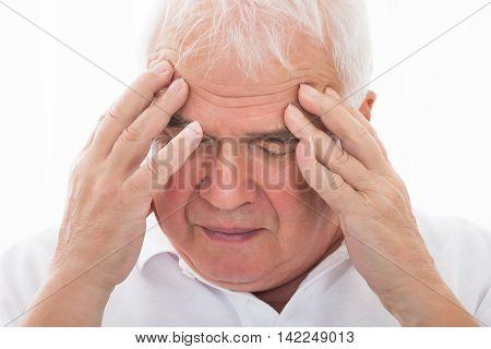 Close-up Of A Senior Man Suffering From Headache