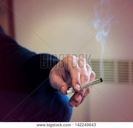 Close up of male hand smoking a hashish joint