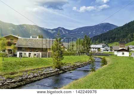 Beautiful view of Alpine Gosauschmied village green valley and river. Traditional austrian houses in Alps mountains. Salzkammergut Austria.