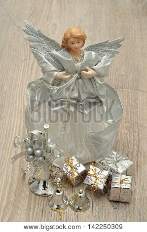 A variety of silver Christmas decorations on a wooden background