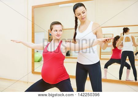pregnant woman with personal trainer doing fitness exercise