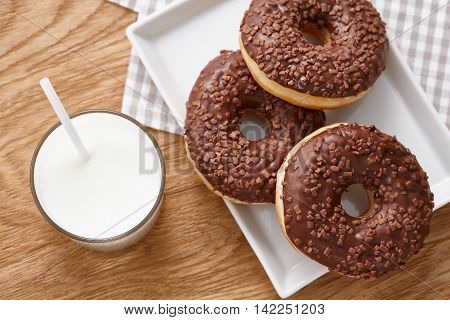 A glass of milk and glazed chocolate donuts on wooden table top view