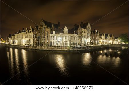 Romantic nocturnal view of a canal in Bruges. Buildings are reflected in the water