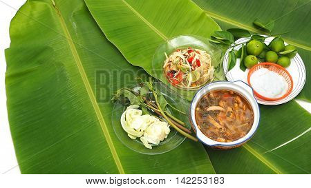 Papaya Slad and Spicy Pork Soup with noodle set Thai Isan favorite herbal green food for diet control have eat with noodles vegetable lemon cabbageThai morning glory all on banana leaf.