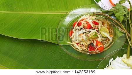 Papaya Slad in glass dish Thai Isan favorite herbal green food for diet control have eat with vegetable lemon cabbageThai morning glory on banana leaf.