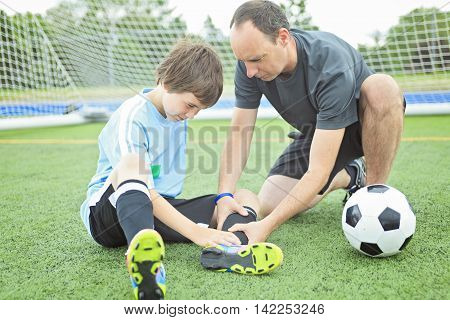 A young soccer player with father check the injury.
