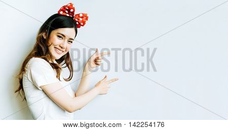 Beautiful asian university or college student woman wearing funny bow headband pointing at copy space on whiteboard background