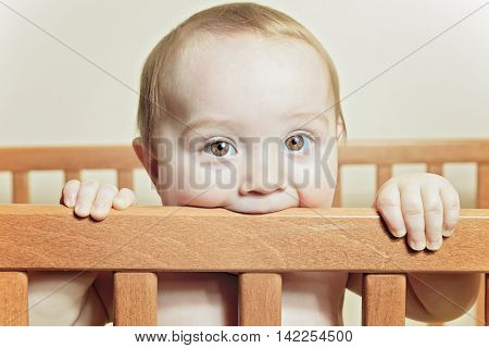 A Funny little baby with beautiful standing in a round white crib