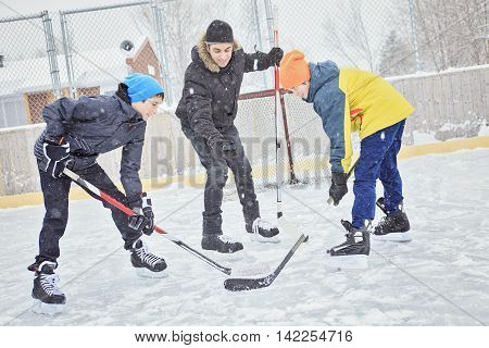 A family playing hockey at the skating rink in winter.