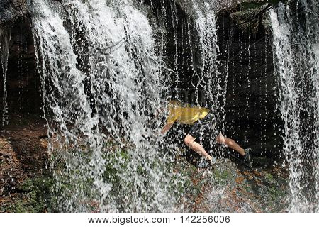 A man navigates the slippery rocks underneath this waterfall.