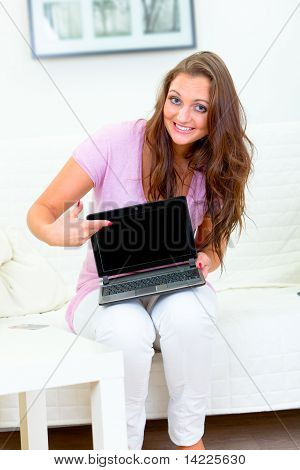 Smiling pretty woman sitting on sofa at home and pointing in laptops blank screen