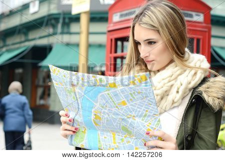 Portrait of a young beautiful tourist looking at a map. Tourism concept. Outdoors.
