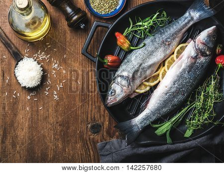Ingredients for cookig healthy fish dinner. Raw uncooked seabass fish with rice, olive oil, lemon slices, herbs and spices on black grilling iron pan over rustic wooden background, top view, copy space, horizontal composition