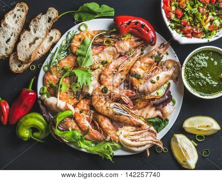 Plate of roasted tiger prawns and pieces of octopus with fresh leek, vegetable salad, peppers, lemon, bread and pesto sauce over black background, top view