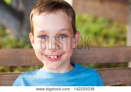 cheerful boy ate chocolate ice cream. happy boy outdoors. mouth smeared with chocolate. the laughter and smiles. the concept of a happy childhood