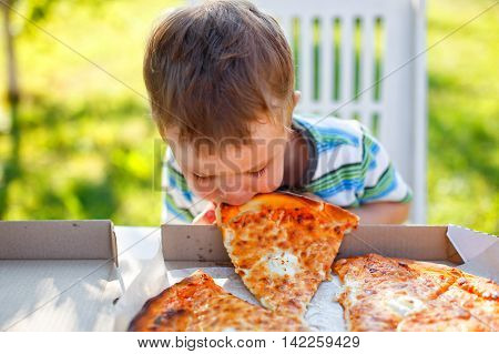 kid biting a slice of pizza. funny toddler eats pizza without using his hands