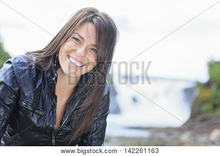 A woman portrait in nature with waterfall on the back