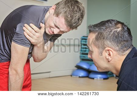 A Portrait of a fitness man reaching for his knee in pain