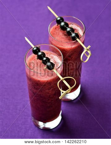 Two glasses of blackcurrant smoothies on purple linen background