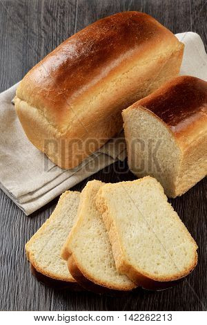 A loaf of wheat bread with slices on wooden background